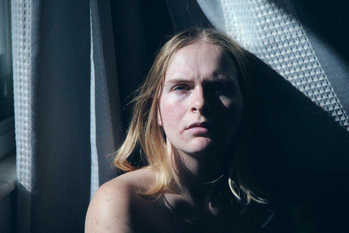 窓際にただずむ女性