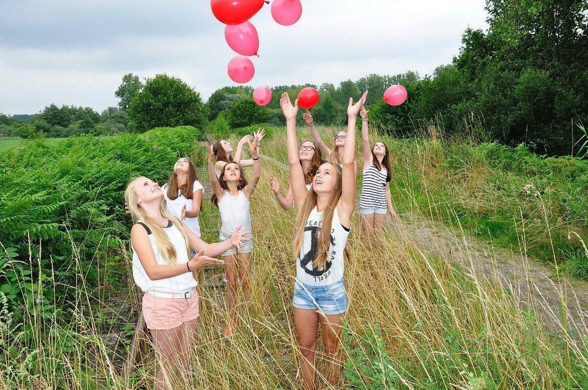 大勢の少女が空中に風船を放っている写真