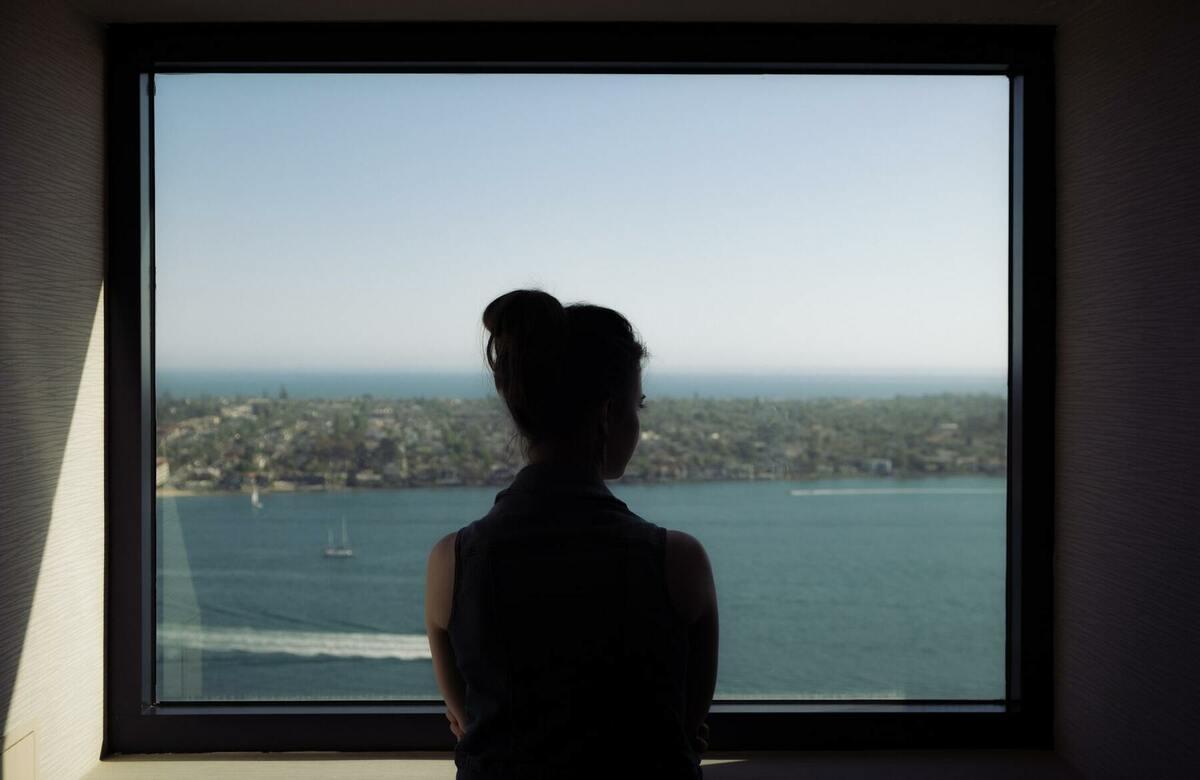 窓から海を見る女性