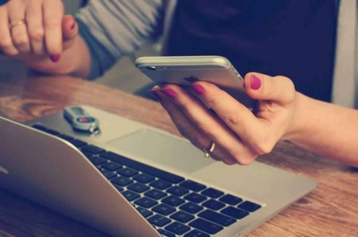 携帯とパソコンを操作する女性