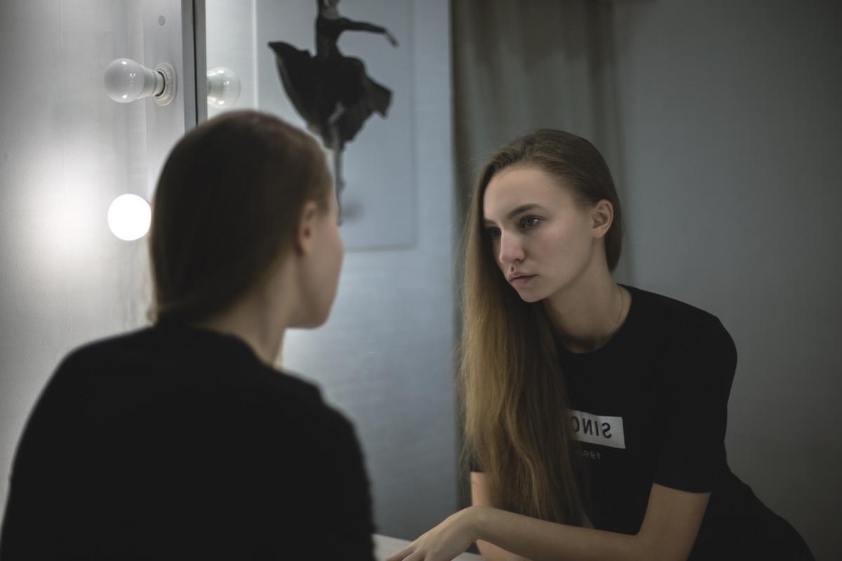 鏡に映る自分を眺める女性