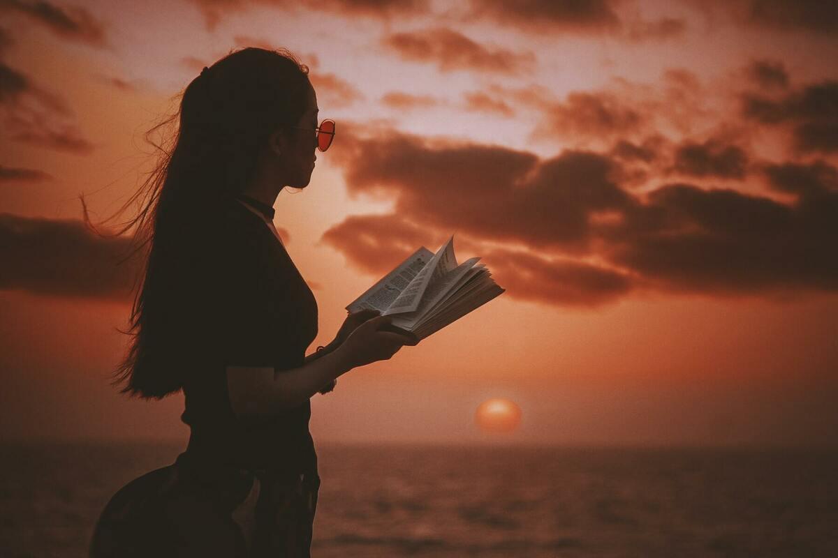 夕陽と本を読む女性