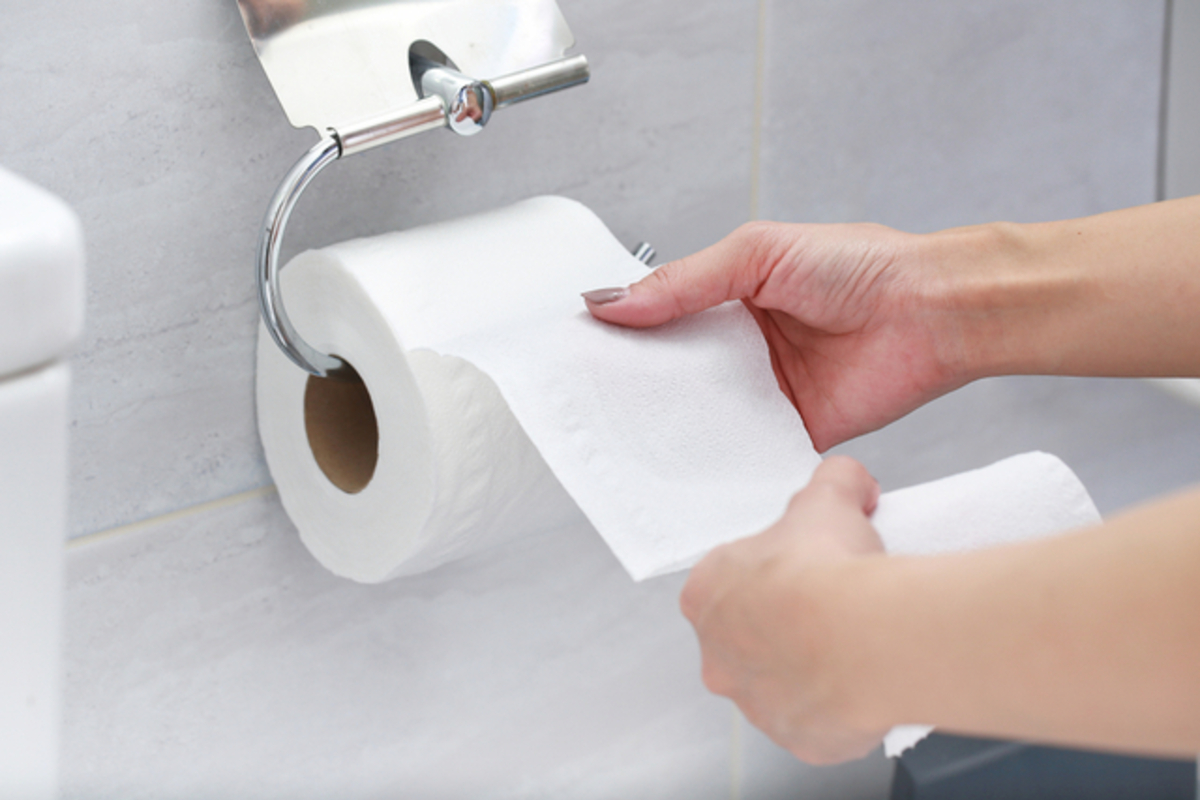 トイレットペーパーを手にする女性