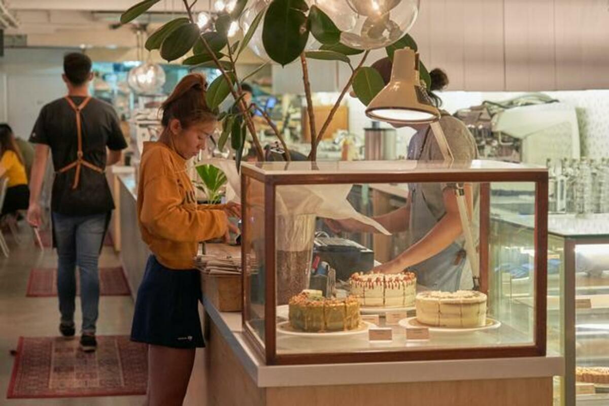 お店でケーキをかう女性