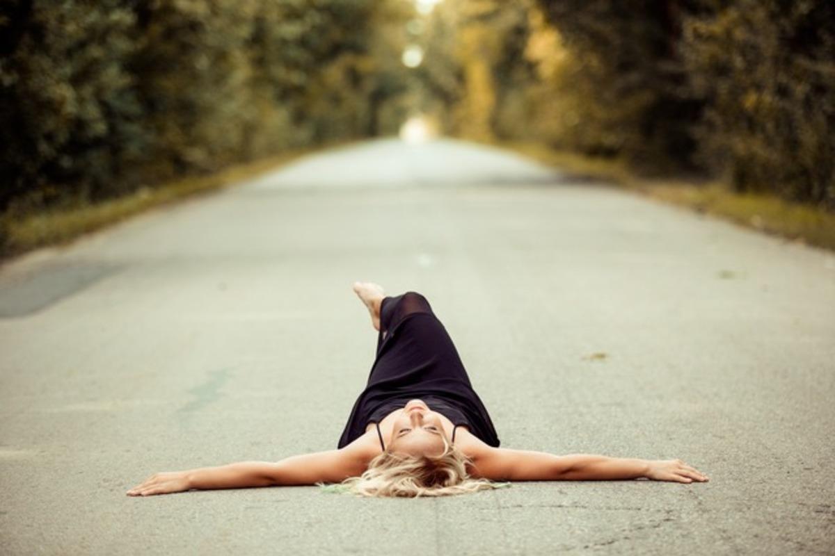 道路に寝そべる女性