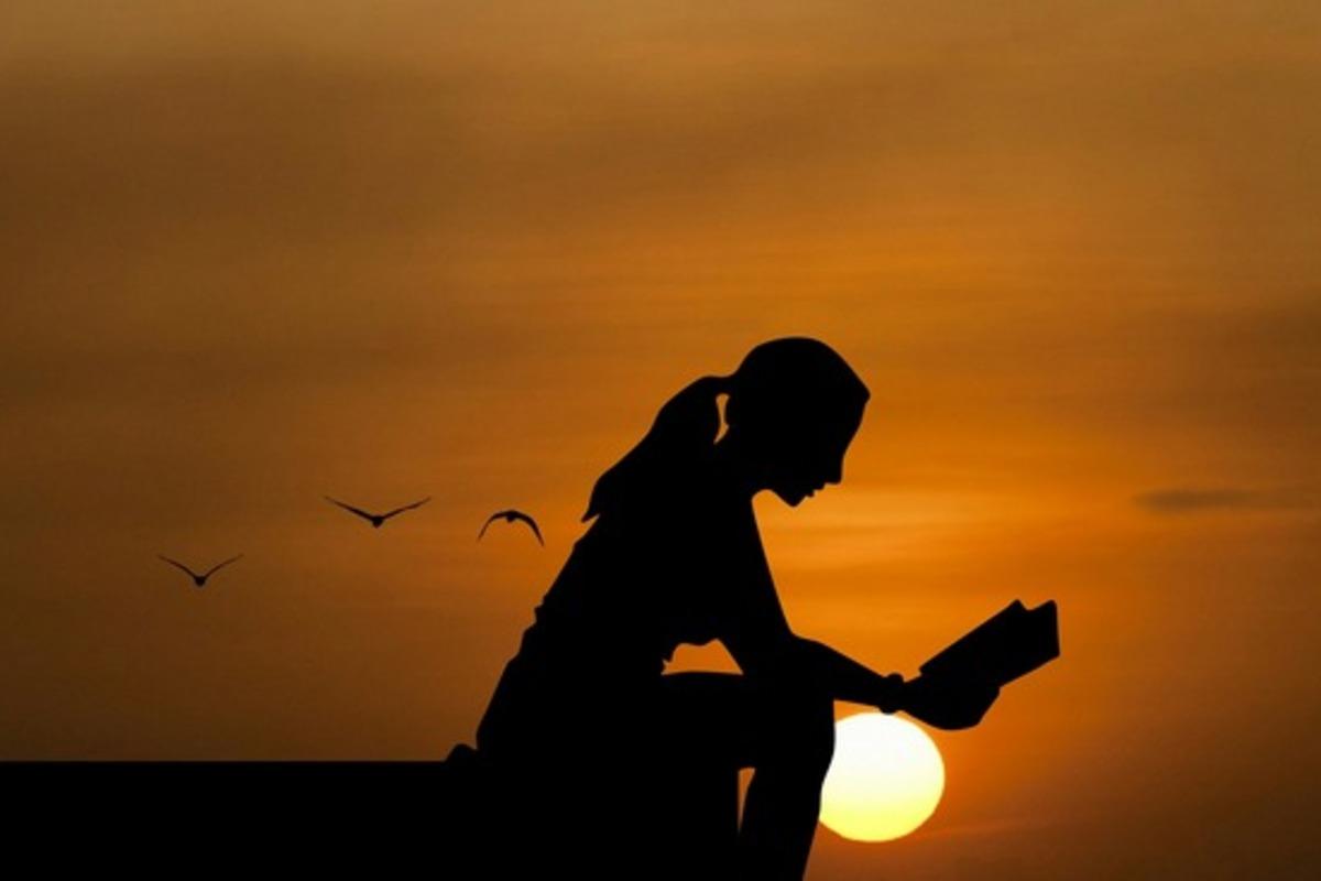 夕日を本を読む女性